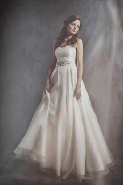 Full length fine art studio portrait of a bride holding the skirt of her dress