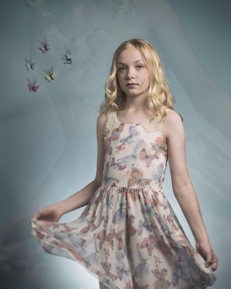 Fine art portrait of a girl in a butterfly dress with butterflies in the background