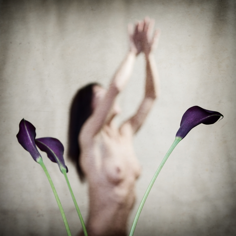 Fine art portrait of female reaching upwards behind a vase of cala lilies