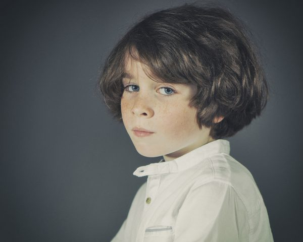 Fine art studio portrait of boy with blue eyes, freckles and brown hair