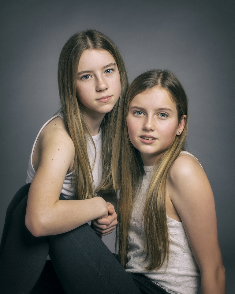 Studio portrait of teenage sisters sitting closely together on the floor