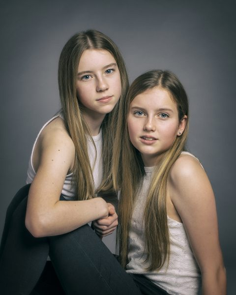 Studio portrait of teenage sisters sitting closely together