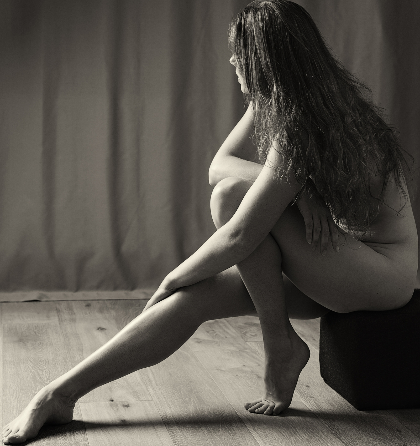Fine art portrait of a female with outstretched leg looking into the light.