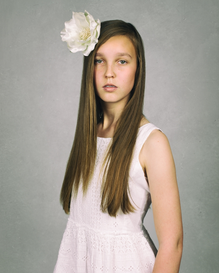 Fine art studio portrait of girl with large flower in her hair