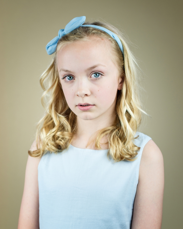 Fine art studio portrait of blond girl with blue eyes, dress and hairband