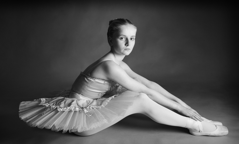 Portrait of a ballet dancer sitting on the floor looking to camera